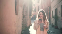 Young happy woman walking in city centre at morning, using smartphone. Girl surfing the Internet, texting with someone