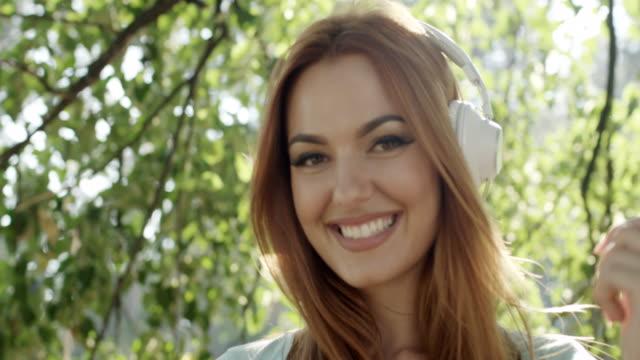 vídeos de stock, filmes e b-roll de jovem mulher feliz com fones de ouvido - cabelo ruivo