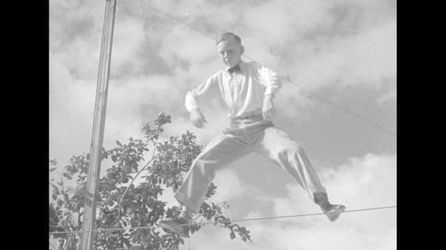young harold barnes walking on tightrope outdoors / two shots of barnes walking on tightrope in kneeling posture / barnes grabbing tightrope and... - tightrope walking stock videos & royalty-free footage