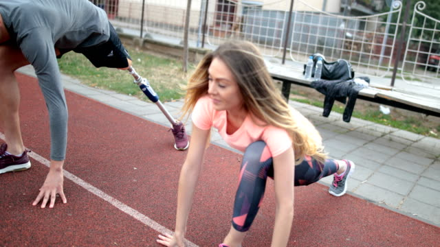 Young health couple doing stretching exercise on track field