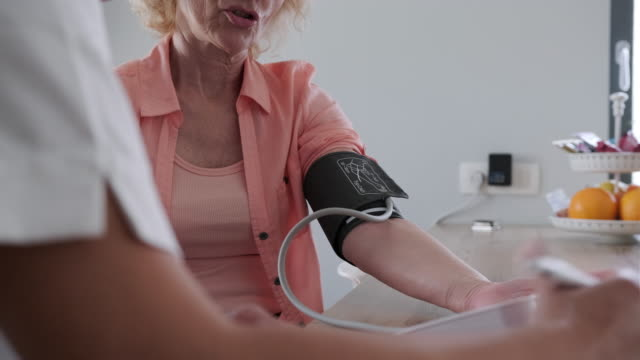 young healthcare worker measuring blood pressure of a senior woman - nursing assistant stock videos and b-roll footage