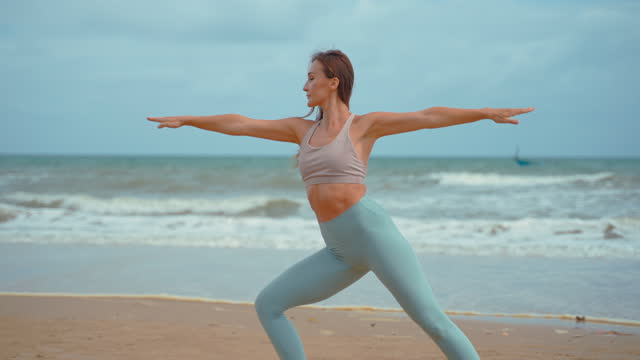 young healthy yoga woman workout yoga pose on the beach at sunrise. strong body concept and good health, benefits of natural environments for physical, spiritual, healthy, relaxing concept. - profile view stock videos & royalty-free footage