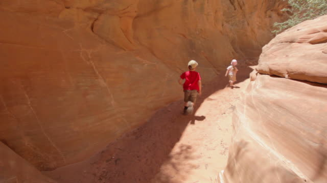 young hiker boy and young hiker girl run past with their mother down a trail in a narrow red-rocked canyon - footpath stock videos & royalty-free footage