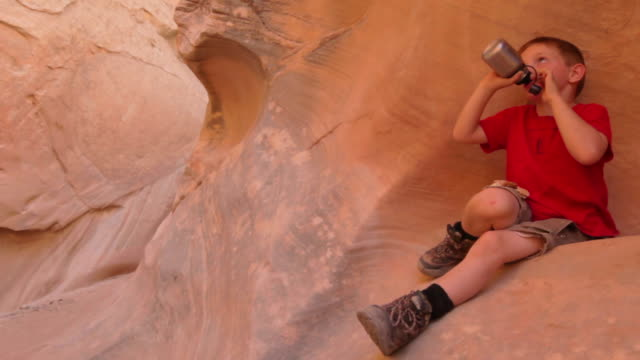 vidéos et rushes de young hiker boy rests on red-rocked canyon wall while drinking water bottle - bouteille d'eau minérale
