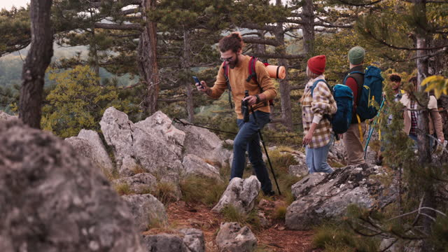young hiker leading his friend through the woods. - wilderness stock videos & royalty-free footage