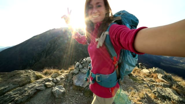 young hiker takes selfie from mountain top - rucksack stock videos and b-roll footage