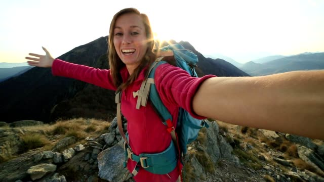 Young hiker taking selfie at mountain top