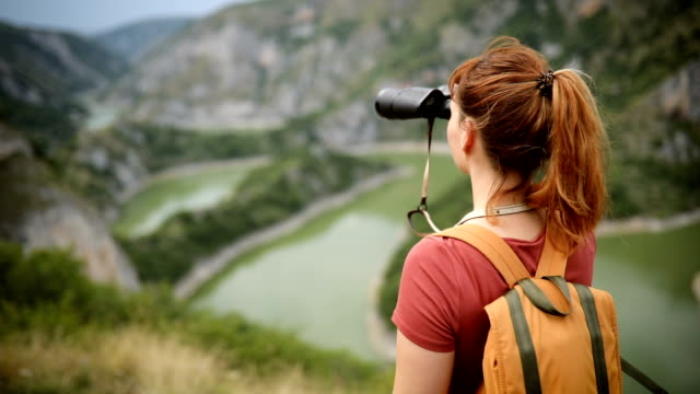 young hiker woman reaches the top of hill, enjoys view - binoculars stock videos & royalty-free footage