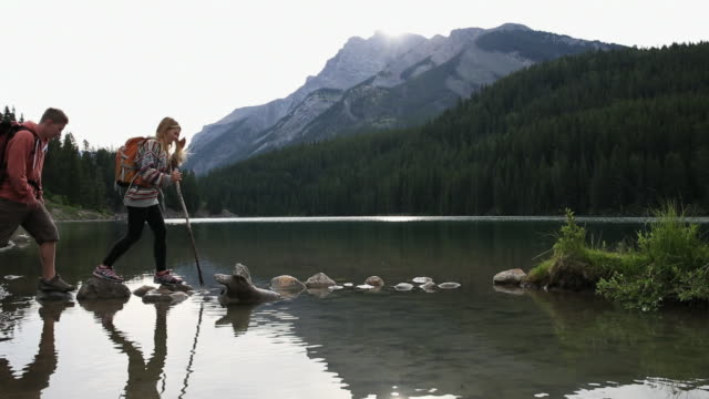 young hiking couple balance along stepping stones, reach island - island stock videos and b-roll footage