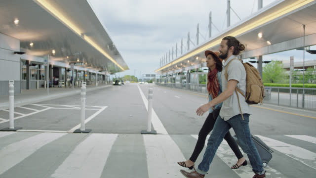 young hip couple holds hands as they walk through crosswalk outside airport at ground transportation. - heimkehr stock-videos und b-roll-filmmaterial