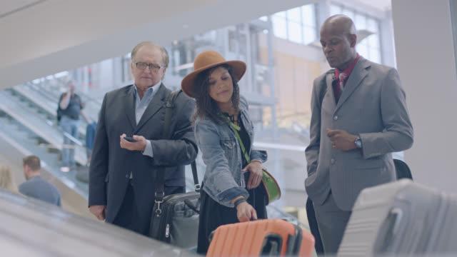 vídeos de stock, filmes e b-roll de young hip female traveler retrieves luggage off conveyor belt in airport baggage claim. - bagagem