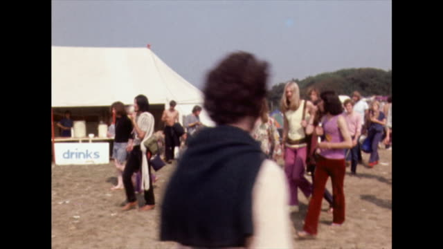 young hippies walk through isle of wight festival site; 1970 - hippy stock videos & royalty-free footage
