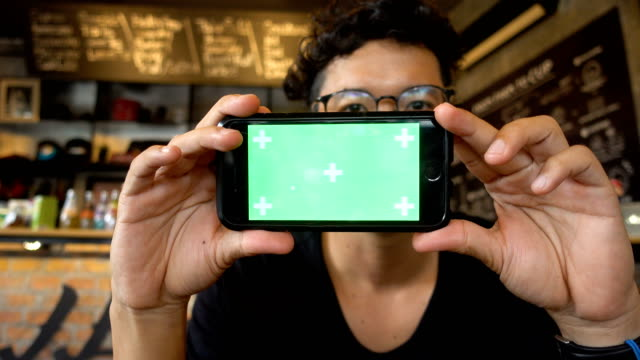 Young hipster Asian man Using mobile phone Green Screen at Coffee shop.