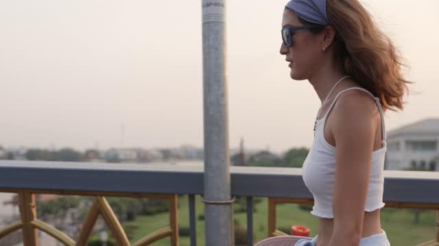 giovane donna asiatica hipster che tiene lo skateboard e cammina sul ponte la sera; rallentatore - persona attraente video stock e b–roll