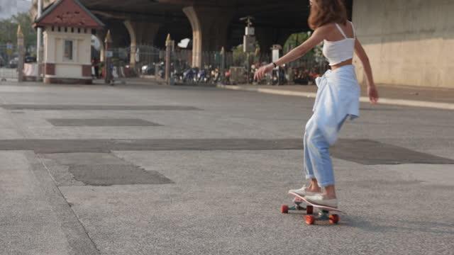 giovane donna asiatica hipster che gioca a skateboard nel parco pubblico sotto il ponte - persona attraente video stock e b–roll