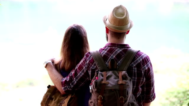 Young hipster couple backpacking looking at the lake