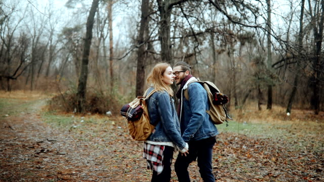 Young hipster couple hiking in nature on cold winter day
