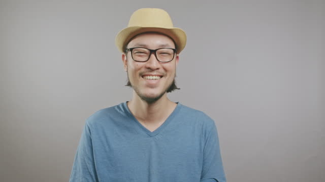 young hipster laughing isolated in grey background. asian man with hat and glasses in front of camera. medium shot. - model object stock videos & royalty-free footage