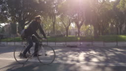 Young hipster man riding bike in park on a road with trees in Rome city centre wearing sunglasses on sunny day slow motion camera car steadycam