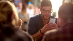 Young hipster man using mobile phone in cafe with friends