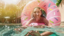 Young hipster millennial girl in sprinkled donut float at pool, smiling look at camera. Young happy woman relaxing on inflatable pool toy in blue swimming pool on sunny day.