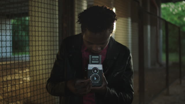 stockvideo's en b-roll-footage met jonge hipster foto schieten met retro camera. - kunstenaar