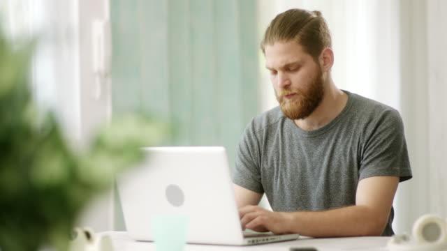 vídeos y material grabado en eventos de stock de joven inconformista con laptop - barba pelo facial
