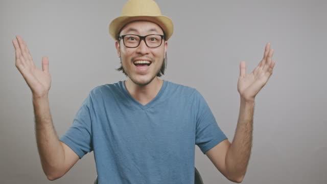 vidéos et rushes de jeune signe de bienvenue de hipster d'isolement dans le fond gris. homme asiatique avec le chapeau et les glaces devant l'appareil-photo. tir moyen. - les bras écartés