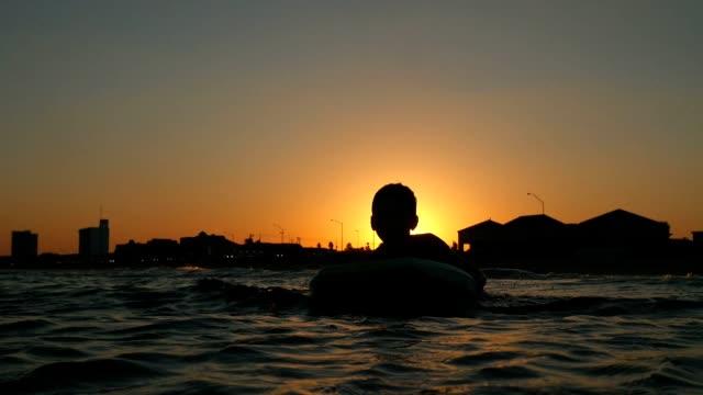 ヒスパニック系の少年海に注いでいるし、日没でボディー ボードでジャンプ