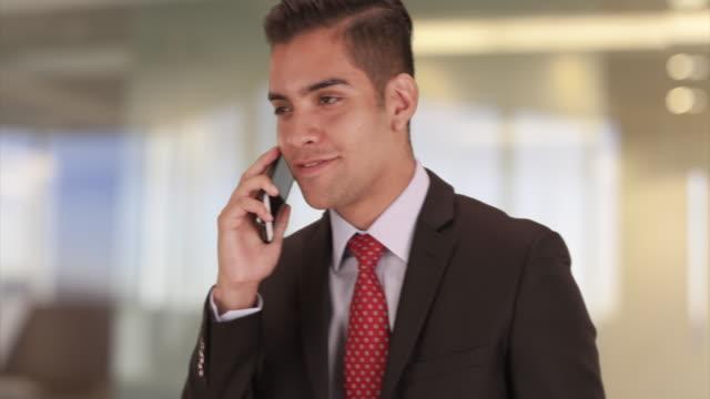 vídeos y material grabado en eventos de stock de young hispanic business professional talking on smartphone in office - vestimenta de negocios formal