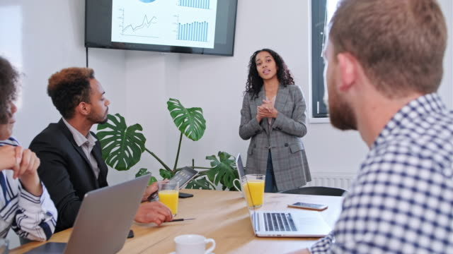 young hispanic businesswoman presenting ideas to colleagues - sales pitch stock videos & royalty-free footage