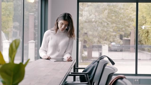 a young hispanic businesswoman uses a digital tablet in open concept office - positive emotion stock videos & royalty-free footage