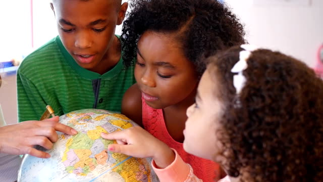 young hispanic daycare teacher helps students study a globe - physical geography stock videos & royalty-free footage