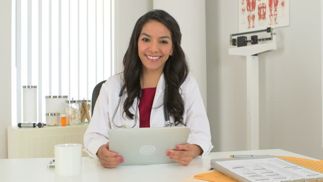young hispanic doctor working on tablet - waist up stock videos & royalty-free footage