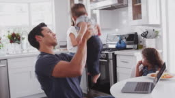 Young Hispanic family in their kitchen, mum cooking at hob, dad lifting baby in the air, close up