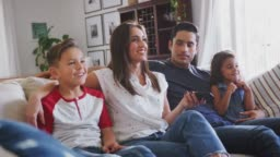 Young Hispanic family sitting on the sofa at home watching TV together, close up