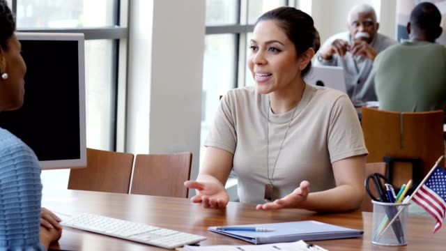 Young Hispanic female soldier talks with financial planner