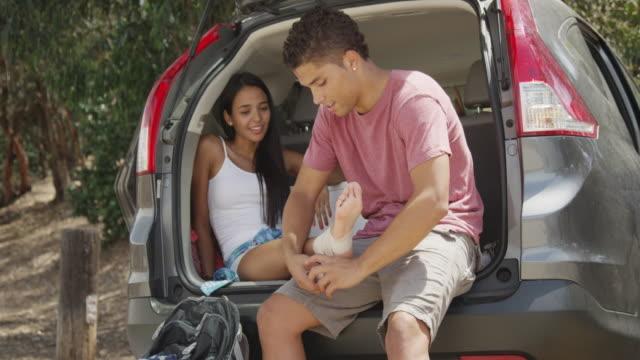 Young Hispanic girl having sprained ankle bandaged