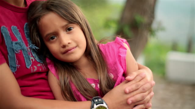 young hispanic girl in big brother's arms smiles at camera - povertà video stock e b–roll