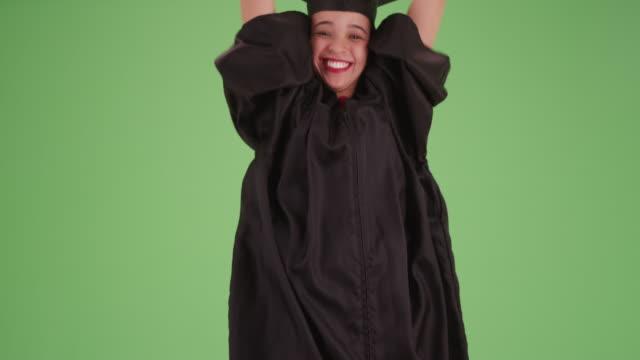 stockvideo's en b-roll-footage met young hispanic girl in her cap and gown on green screen - mortelplank