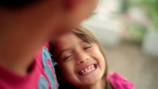 Young hispanic girl laughs in older brother's arms