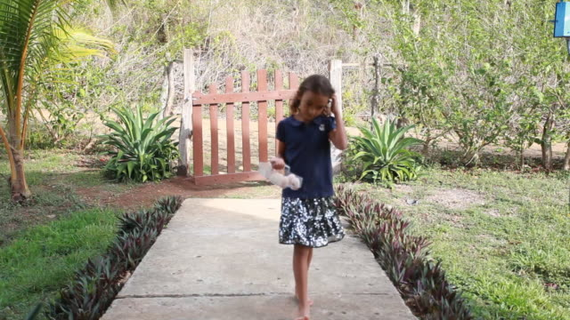 vidéos et rushes de young hispanic girl opens gate and walks through carrying a batch of eggs in an egg holder - kelly mason videos