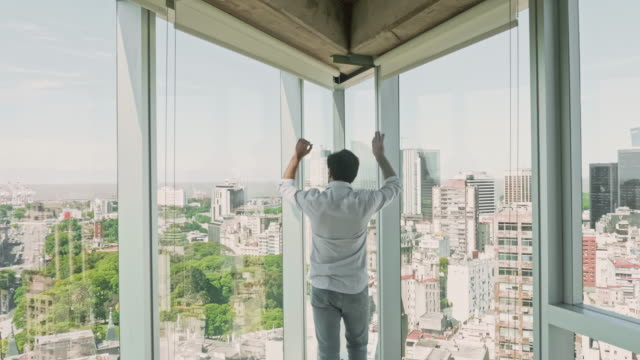 young hispanic male entrepreneur looking out office window - corner stock videos & royalty-free footage
