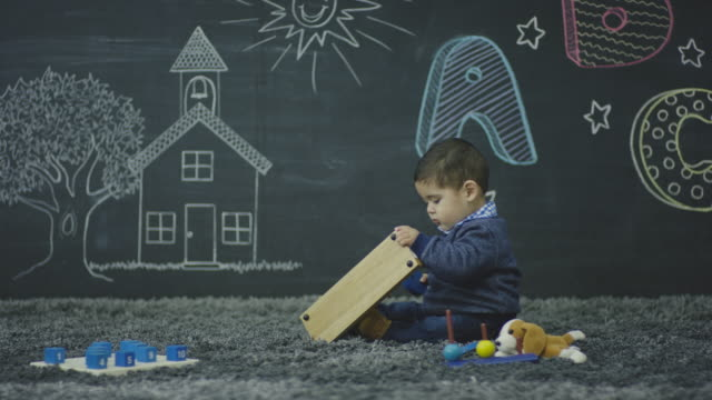 Young Hispanic Male Toddler Playing with Baby Toys In Front of a Wall of Chalk Drawings