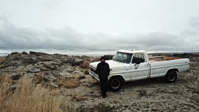 young hispanic man at water's edge with his vintage pickup - ford truck stock videos and b-roll footage