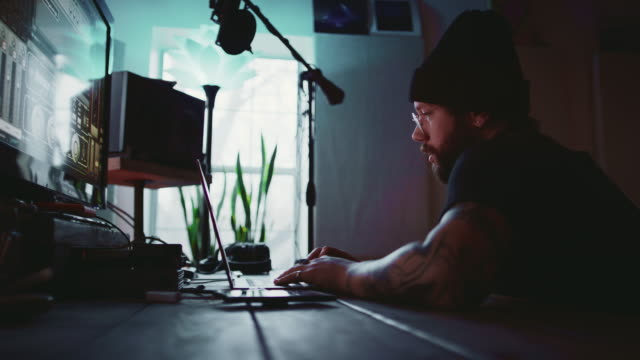 a young hispanic man in his thirties with a beard, tattoos, and an earring works at a laptop computer while talking someone else next to music recording equipment in a recording studio - recording studio stock videos & royalty-free footage