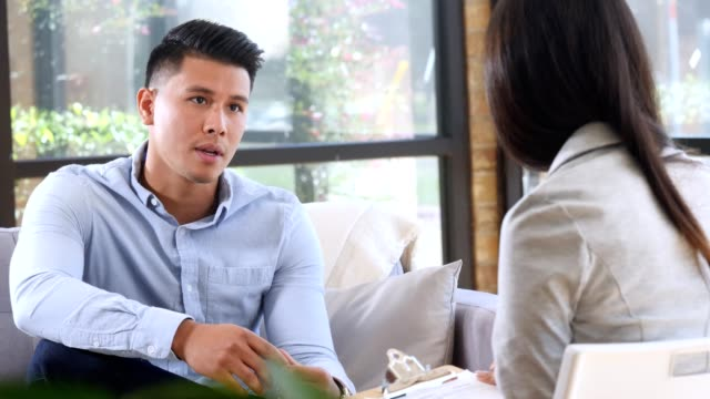 young hispanic man talks with female therapist - young men stock videos & royalty-free footage