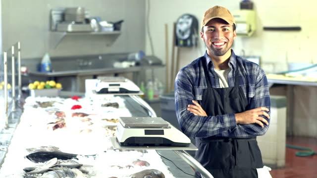 vídeos de stock e filmes b-roll de young hispanic man working in fish market - empregado de balcão