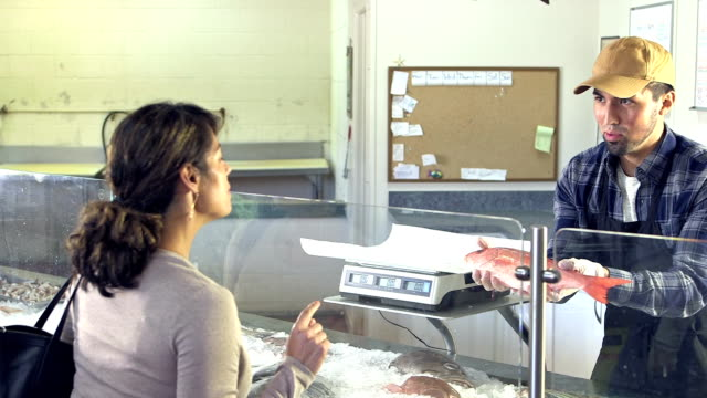 young hispanic man working in fish store helps customer - fish market stock videos and b-roll footage