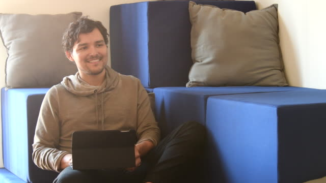 Young hispanic man working on tablet in casual coworking space